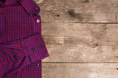 A checkered men shirt is on wooden background Royalty Free Stock Photos