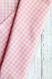 Checkered napkin on white wooden table Stock Photography