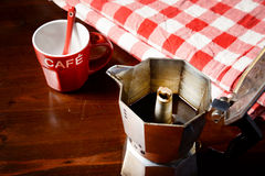 Checkered napkin on wooden table with red coffee cup. Top view of checkered napkin on wooden table with red coffee cup and  vintage coffeepot Royalty Free Stock Image