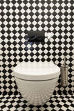 Checkered pattern in toilet. Toilet with a checkered pattern wall, closeup Royalty Free Stock Images