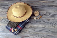 Checkered plaid for a picnic, wicker hat and seashells on a wood. New, waterproof, checkered plaid for a picnic and camping, wicker hat and seashells on a wooden stock image