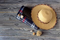 Checkered plaid for a picnic, wicker hat and seashells on a wood. New, waterproof, checkered plaid for a picnic and camping, wicker hat and seashells on a wooden royalty free stock images