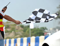 Checkered racing flag. Checkered race flag in hand royalty free stock images