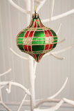 Checkered red gold and green Christmas Bobble. Hanging Christmas bobble checkered. Red green and gold color. Hanging on a white tree Stock Image