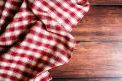 Checkered red napkin on an old wooden brown background, top view. Image with copy space. Kitchen table with a towel - top view wit. H copy space Royalty Free Stock Images