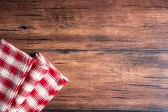 Checkered red napkin on an old wooden brown background, top view. Image with copy space. Kitchen table with a towel - top view wit. H copy space Stock Images