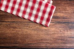 Checkered red napkin on an old wooden brown background, top view. Image with copy space. Kitchen table with a towel - top view wit. H copy space Stock Photos