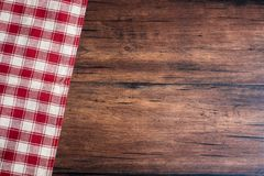 Checkered red napkin on an old wooden brown background, top view. Image with copy space. Kitchen table with a towel - top view wit. H copy space Royalty Free Stock Photos