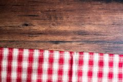 Checkered red napkin on an old wooden brown background, top view. Image with copy space. Kitchen table with a towel - top view wit Royalty Free Stock Photo