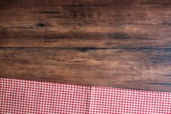 Checkered red napkin on an old wooden brown background, top view. Image with copy space. Kitchen table with a towel - top view wit Royalty Free Stock Photos
