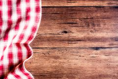 Checkered red napkin on an old wooden brown background, top view. Image with copy space. Kitchen table with a towel - top view wit. H copy space stock photography