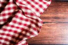 Checkered red napkin on an old wooden brown background, top view. Image with copy space. Kitchen table with a towel - top view wit. H copy space Royalty Free Stock Image