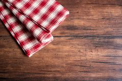 Checkered red napkin on an old wooden brown background, top view. Image with copy space. Kitchen table with a towel - top view wit. H copy space Stock Photo