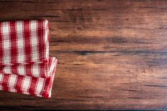Checkered red napkin on an old wooden brown background, top view. Image with copy space. Kitchen table with a towel - top view wit. H copy space Stock Image