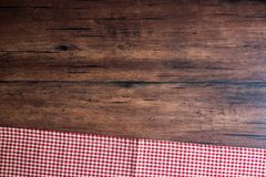 Checkered red napkin on an old wooden brown background, top view. Image with copy space. Kitchen table with a towel - top view wit. H copy space Royalty Free Stock Photography