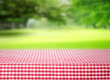 Checkered red tablecloth emty space table green background. Street cafe empty space table. Red checkered tablecloth texture top view background.Product display Stock Photos
