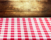 Checkered red tablecloth over wooden background Stock Photography