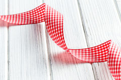 Checkered ribbon on white wooden table Stock Photos