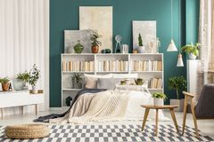 Checkered rug in stylish bedroom. Checkered rug and modern wooden furniture in a stylish bedroom interior for art and nature lover royalty free stock image