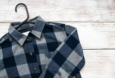 Checkered shirt with hanger. On a old wooden table Stock Image