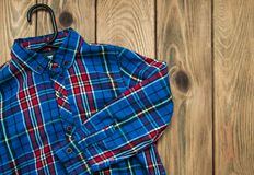 Checkered shirt  with hanger. On a old wooden table Stock Photos