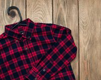 Checkered shirt  with hanger. On a old wooden table Royalty Free Stock Photo
