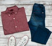Checkered shirt and jeans. On a old wooden table Royalty Free Stock Images
