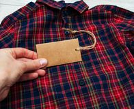 Checkered shirt with tag. Checkered shirt on a table with tag Royalty Free Stock Image