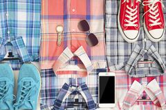 Flat lay different checkered shirts witn phone and accesories. Casual women clothing set Stock Images