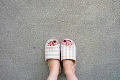 Checkered Slippers, Selfie Woman's Pink Home Slippers Feet Nail polish on Concrete Background. Great for Any Use Royalty Free Stock Photo