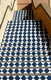 Checkered Stairs. An outdoor staircase features a blue and white diamond-shaped checkered pattern royalty free stock photo