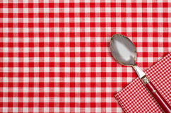 Checkered table cloth with red and white checks and a spoon. Spoon and napkin on a  checkered table cloth with red and white checks Stock Image