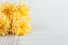 Checkered table napkin with yellow flowers. White table copy space Stock Photography