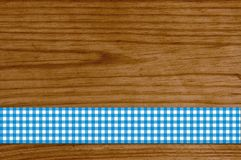 Checkered tablecloth blue white on wooden plank. Brown wooden background with checkered tablecloth blue white Royalty Free Stock Image