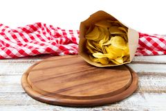Checkered tablecloth pack of potato chips and empty pizza board on wooden table isolated on white background stock photo