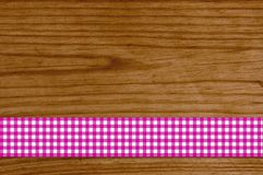 Checkered tablecloth pink white on wooden plank. Brown wooden background with checkered tablecloth pink white Royalty Free Stock Photography
