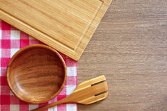 Checkered tablecloth, wooden spoon and a bowl on a wooden table. Royalty Free Stock Photos