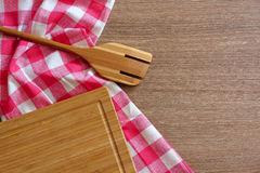 Checkered tablecloth, wooden spoon and a chopping board on a wooden table. Stock Photos