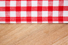 Checkered tablecloth on wooden table. The checkered tablecloth on wooden table Stock Photography
