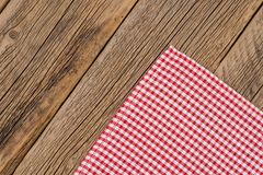 The checkered tablecloth on wooden table. Top view Royalty Free Stock Photo