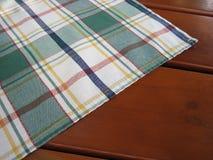 Checkered Tischdecke auf hölzerner Tabelle Lizenzfreie Stockbilder