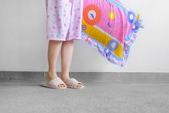 Checkered Warm Slipper. Female Standing in Pink Pajamas Pants and Shoes Holding A Pink Pillow on The Floor Background. Great For Any Use Stock Photos