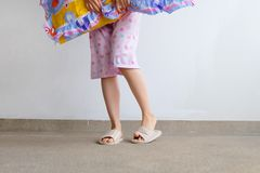 Checkered Warm Slipper. Female Standing in Pink Pajamas Pants and Shoes Holding A Pink Pillow on The Floor Background. Great For Any Use Stock Photo