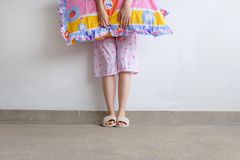 Checkered Warm Slipper. Female Standing in Pink Pajamas Pants and Shoes Holding A Pink Pillow on The Floor Background. Great For Any Use Stock Image