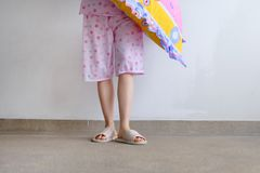 Checkered Warm Slipper. Female Standing in Pink Pajamas Pants and Shoes Holding A Pink Pillow on The Floor Background. Great For Any Use Royalty Free Stock Photo