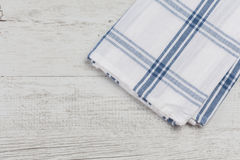 Checkered white blue kitchen towel on white rustic wooden background Stock Photography