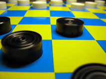 Checkers. Black and white draughts on the draughtboard Stock Image