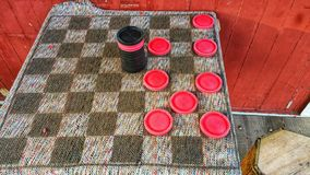 Checkers anyone?! Outdoor cloth board with large red and black checkers. Red wood wall. Competition. royalty free stock photo