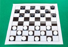 Checkers on black and white checkered sheet board. On green baize table stock images
