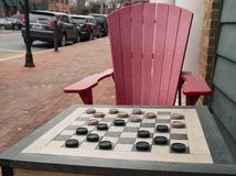 Checkers game in public on sidewalk. Step up and take a seat to play the game with a friend or stranger royalty free stock images